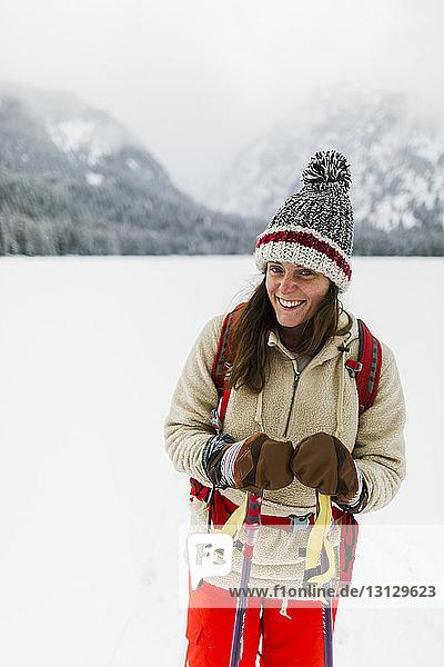 Porträt einer lächelnden Frau  die auf einem schneebedeckten Feld wandert