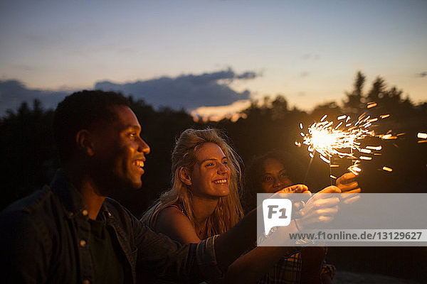 Happy friends holding illuminated sparklers at dusk