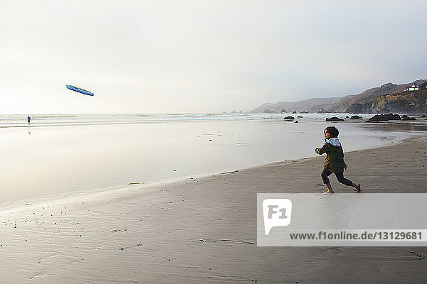Boy throwing Frisbee while standing on shore at beach against sky