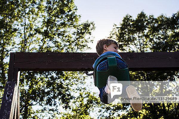 Niedrigwinkelansicht eines gegen den Himmel schwingenden Jungen auf einem Spielplatz