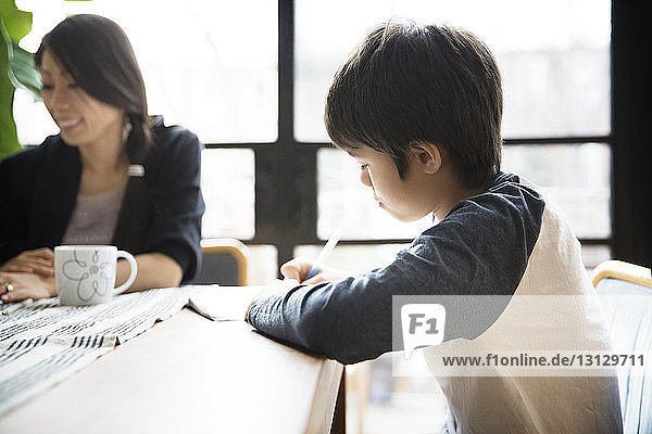 Boy studying while sitting with mother by table at home