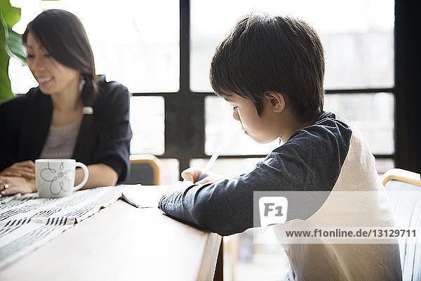 Junge lernt  während er zu Hause mit der Mutter am Tisch sitzt