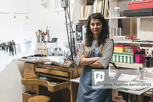 Portrait of confident female artisan with arms crossed standing against shelves in workshop
