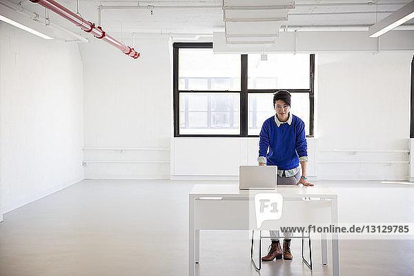 Porträt einer Geschäftsfrau mit Laptop-Computer am Stehtisch im neuen Büro
