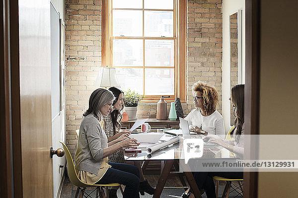 Multi-ethnische kreative Geschäftsfrauen diskutieren im Sitzungssaal