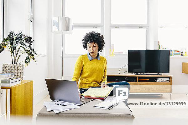 Seriöse Geschäftsfrau benutzt Laptop-Computer  während sie im Büro sitzt