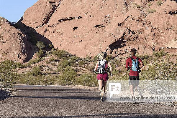 Rückansicht von Wanderern mit Rucksäcken  die bei Sonnenschein auf der Strasse gegen Felsformationen laufen