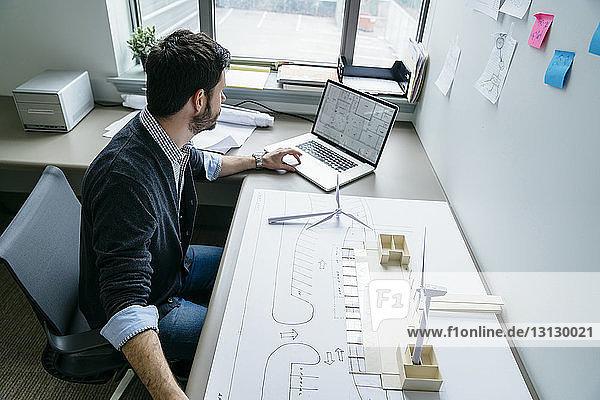 Hochwinkelansicht eines Geschäftsmannes mit Laptop beim Aufstellen von Windturbinenmodellen