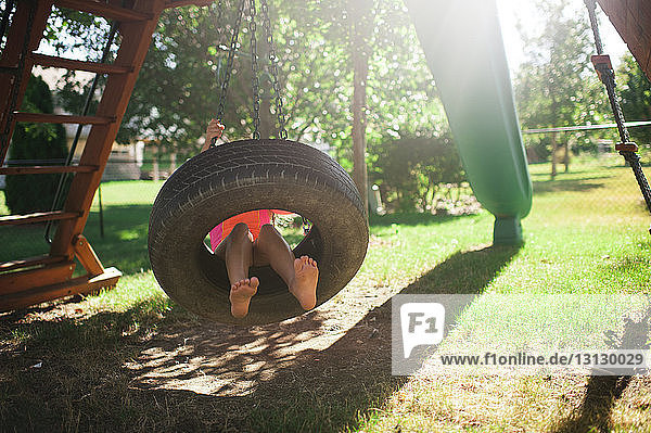 Low section of boy swinging in tire swing at playground