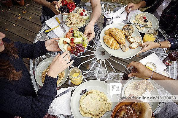 Schrägaufnahme von Freunden  die während des Frühstücks am Tisch vorbeischauen