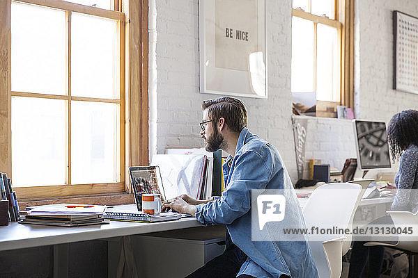 Geschäftsmann benutzt Laptop  während er am Schreibtisch im Kreativbüro sitzt