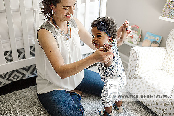 Hochwinkelansicht einer Mutter  die die Hände der Tochter hält  während sie zu Hause auf dem Boden sitzt