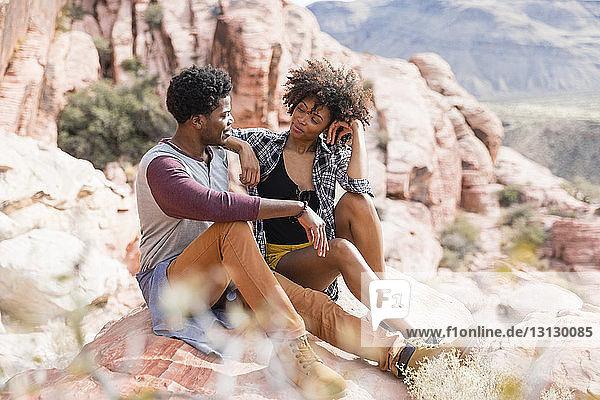 Paar  das sich bei sonnigem Wetter auf einer Felsformation sitzend anschaut