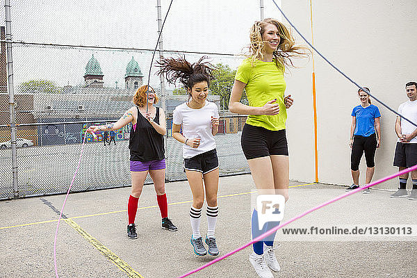 Friends looking at women performing double Dutch against fence