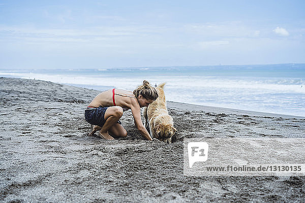 Full length of woman and Labrador Retriever digging on shore at beach