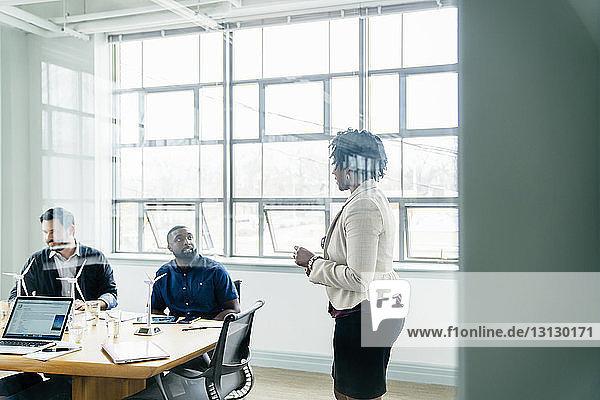 Seitenansicht einer Geschäftsfrau  die mit Kollegen diskutiert  durch Fenster gesehen