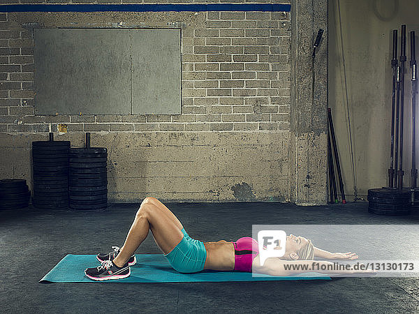 Side view of female athlete exercising at gym
