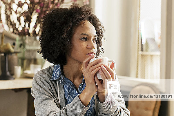 Thoughtful woman with mug at home