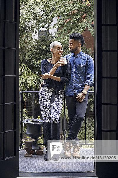 Happy couple talking while standing in balcony seen through doorway