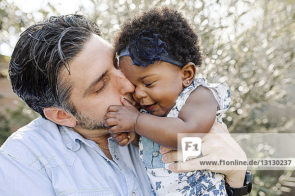 Nahaufnahme eines glücklichen Vaters  der seine Tochter küsst  während er auf dem Hof sitzt