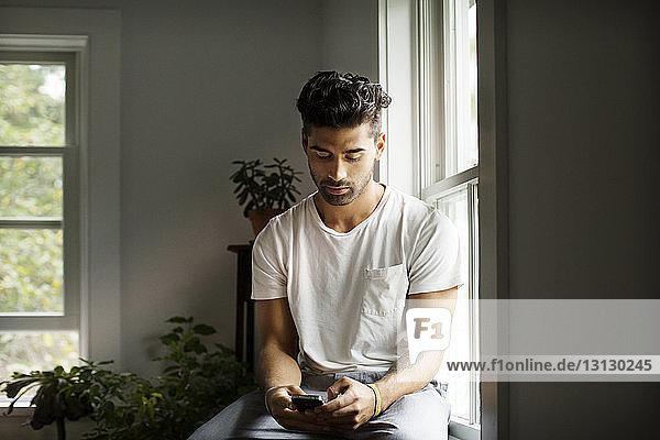Junger Mann benutzt Smartphone  während er zu Hause am Fenster sitzt