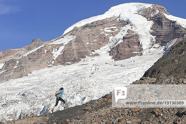 Rucksacktouristin geht auf Berg gegen Himmel