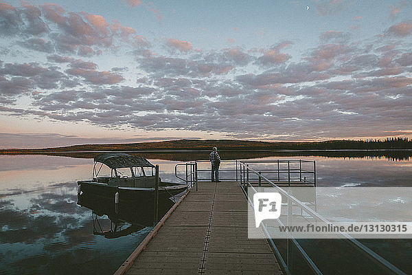 Man standing on pier over river against cloudy sky during sunset