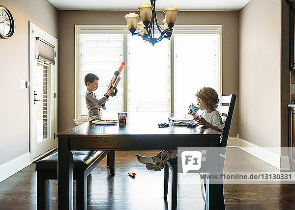 Boy drinking while brother playing with toy gun at home