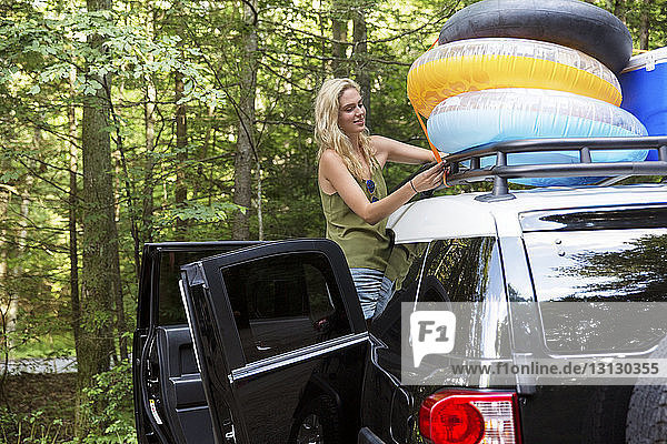 Woman tying inner tubes on roofrack of car in forest