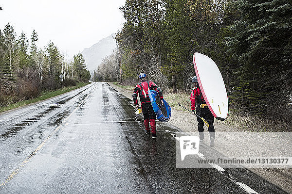 Rear view of paddlers carrying paddleboards while walking on wet road