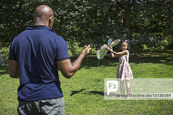 Happy daughter and father playing with kite on grassy field