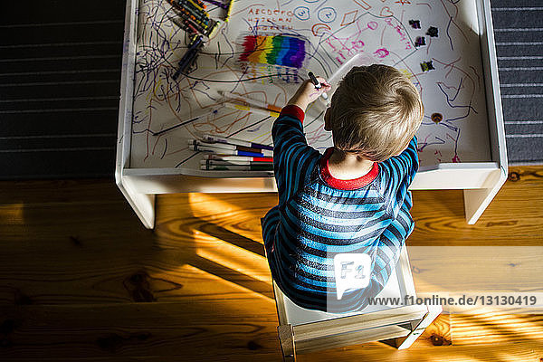 Hochwinkelansicht eines Jungen  der am Tisch sitzend zeichnet