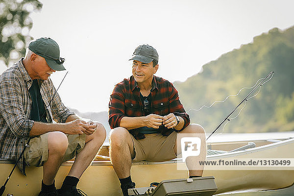 Smiling friends talking while sitting by fishing rods on boat at lakeshore