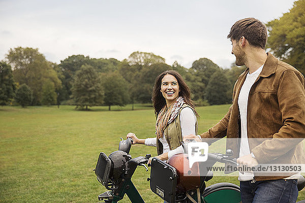 Happy couple talking while walking with bicycles in park
