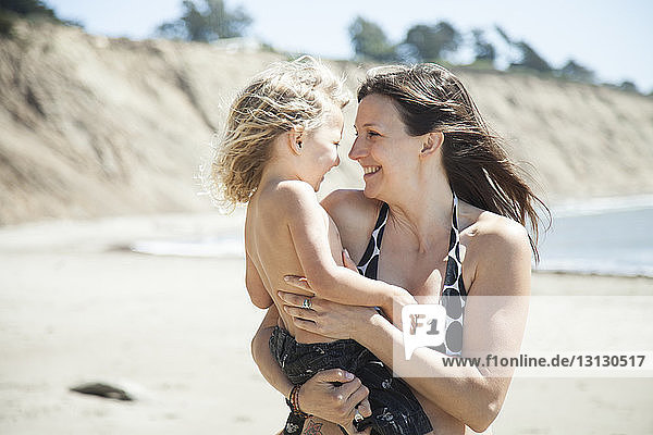 Happy mother and daughter at beach on sunny day