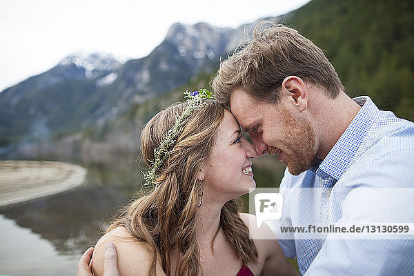 Close-up of smiling young couple looking each other face to face while touching their foreheads at Silver Lake Provincial Park