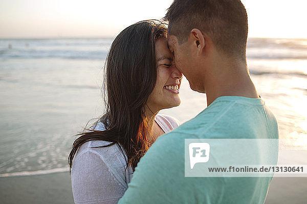 Glückliches Paar mit geschlossenen Augen am Strand bei Sonnenuntergang