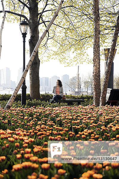 Geschäftsfrau sitzt auf Bank mit blühenden Tulpen im Vordergrund im Park