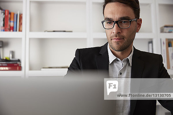 Businessman using laptop computer in home office
