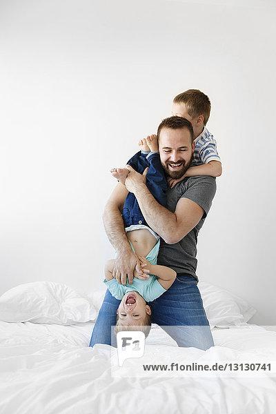 Fröhlicher Vater spielt zu Hause mit Söhnen im Bett an der Wand