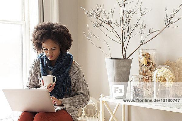 Frau benutzt Laptop-Computer  während sie zu Hause auf einem Stuhl sitzt