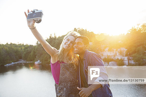 Friends taking selfie through camera by lake during sunset