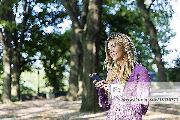 Nachdenkliche Frau hört Musik im Park