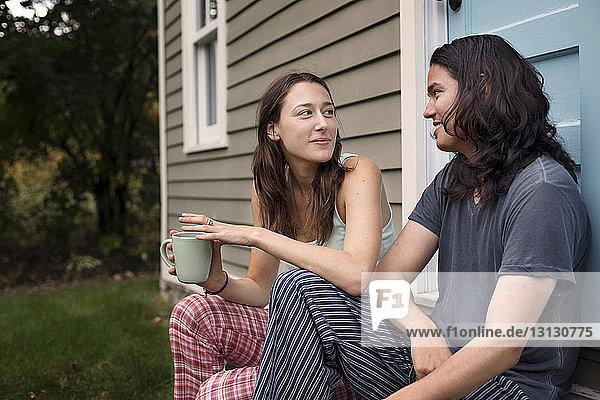 Paare,  die sich beim Entspannen vor dem Haus anschauen