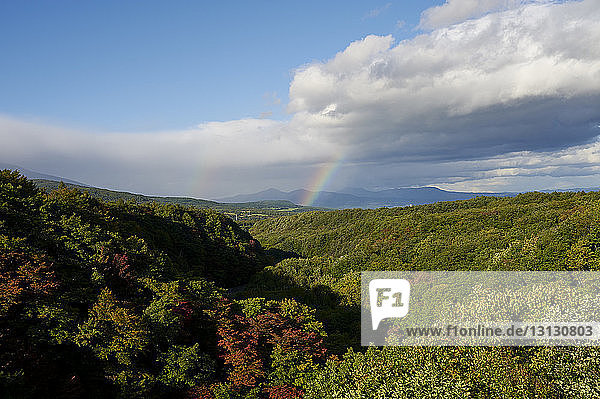 Landschaftliche Ansicht des Hakkoda-Gebirges gegen Regenbogen und bewölkten Himmel