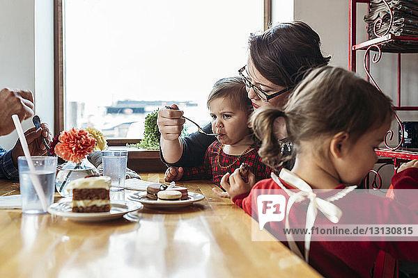 Mutter füttert Mädchen  während sie mit der Familie am Restauranttisch sitzt