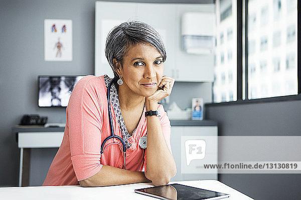 Porträt einer selbstbewussten Ärztin  die in der Klinik am Schreibtisch lehnt Porträt einer selbstbewussten Ärztin, die in der Klinik am Schreibtisch lehnt
