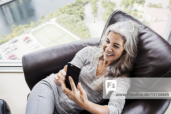 Overhead view of happy mature woman taking selfie while sitting on armchair at home