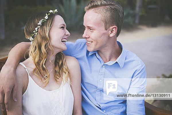 Glückliches Paar schaut sich an  während es auf einer Parkbank sitzt