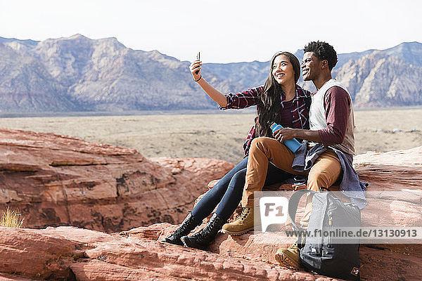 Fröhliche Freunde  die bei Sonnenschein auf Felsformationen vor klarem Himmel sitzen